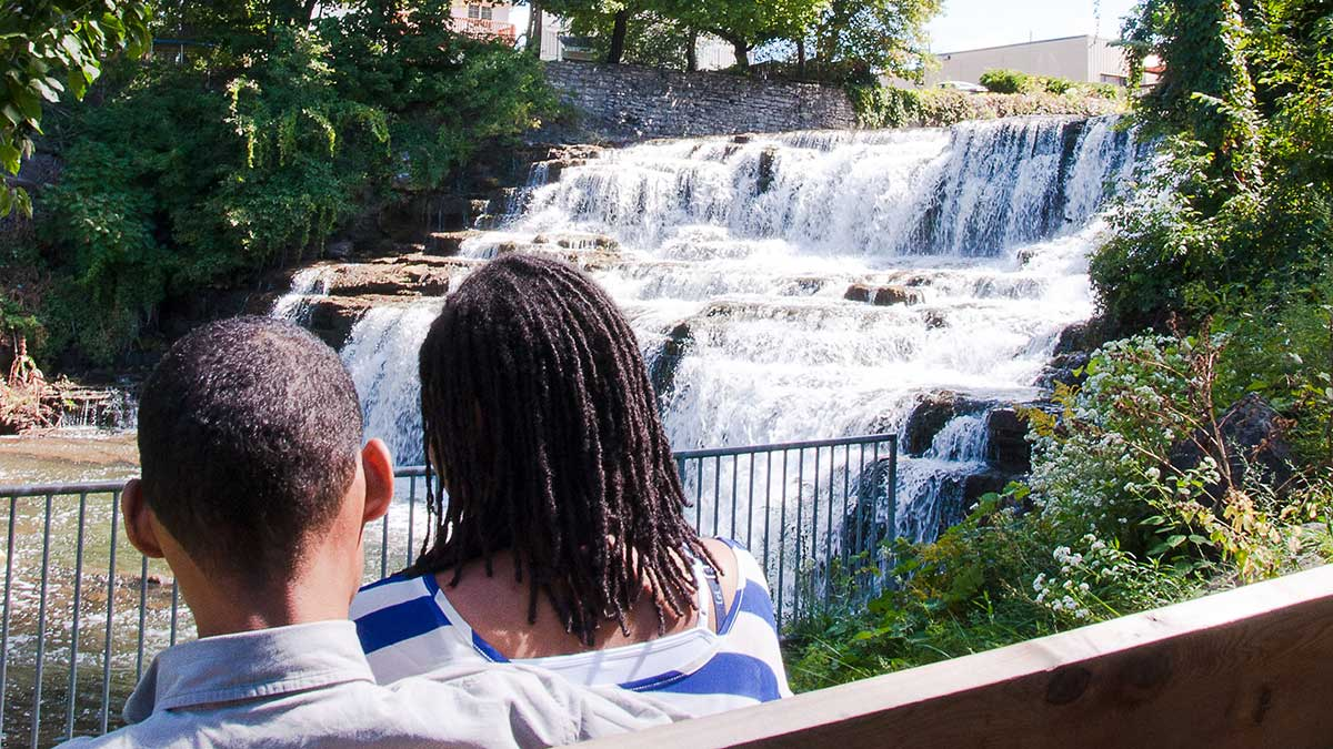 Enement Photo Of Man Holding Woman In Arms With Large Waterfall And Lush Green Forest