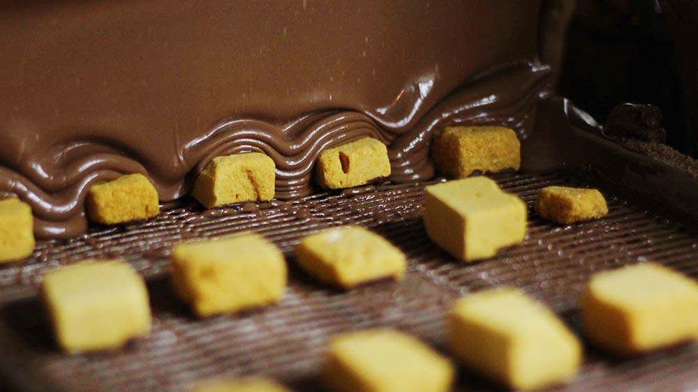 Sponge candy being coated in chocolate