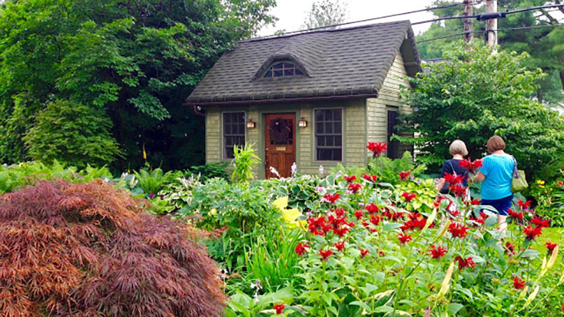 On Darwin Drive In Snyder The Home Of Coyne DiNezza Garden Is A Site To Behold Curve Edged Roof Stone English Cottage