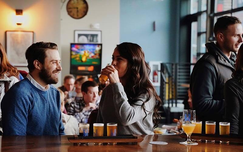 People enjoying beer flights at a bar